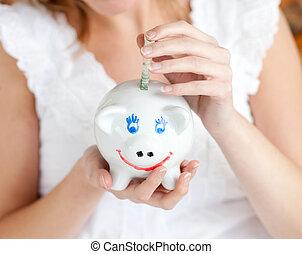 Close-up of a woman saving money in a piggy-bank