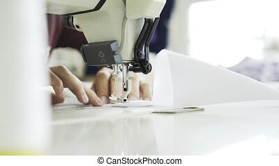 Close up of a woman sewing a white shirt at a factory