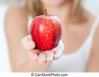 Close-up of a woman showing an apple