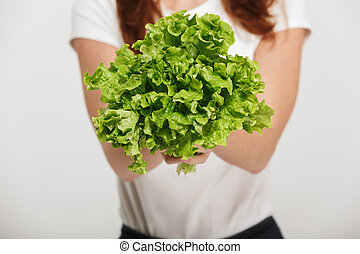Close up of a woman showing fresh green salad leaves