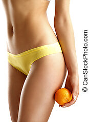 Close up of a woman showing hips with a fruit in her hand on...