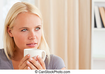 Close up of a woman sitting on a sofa with a cup of tea