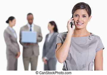 Close-up of a woman smiling on the phone and co-workers with a laptop in the background