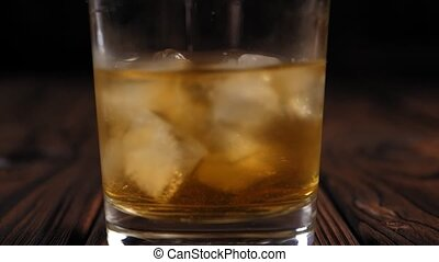 Close-up of a woman twirling a glass of whiskey with ice on a wooden background.