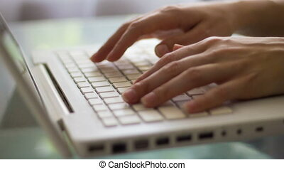 Close-up of a woman typing on a laptop keyboard