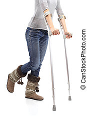 Close up of a casual woman walking with crutches isolated on a white background