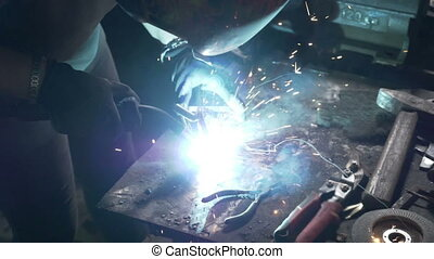 Close up of a woman welder or blacksmith hands working in a...