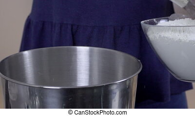 Close-up of a woman with a spatula pours flour into a bowl.