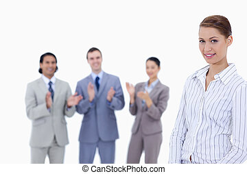 Close-up of a woman with business people applauding while watching her against white background