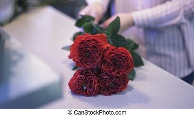 Close up of a woman working in a florist shop making a bouquet of roses