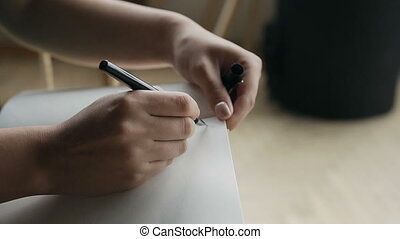 Close-up of a woman writing a hand on an empty notebook with a pen.