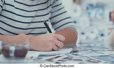 Close-up of a woman writing in a notebook. Notepads on the table.