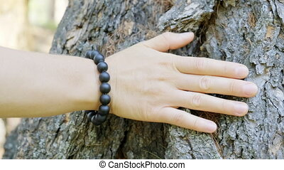 Close-up of a woman's hand with a bracelet, which is carefully stroking the tree