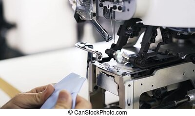 Close up of a worker attaching a button to a shirt at a factory