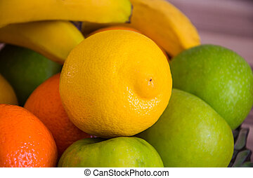 Close up of a yellow lemon between other green and orange fruits