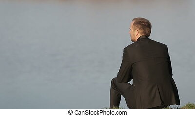 Close up of a young adult's man back with look of concern with blue lake on background.