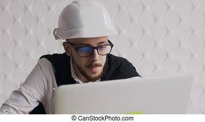 Close-up of a young architect wearing a beard and glasses, wearing a white head helmet for his own safety and works on a laptop over a new architectural project