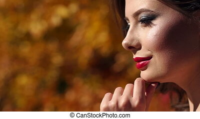 Close-up of a young beautiful girl in a evening dress walking in the autumn park