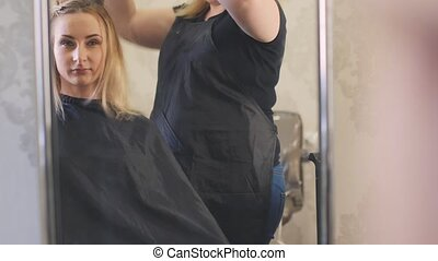 Close up of a young blonde woman in luxury beauty parlour after finishing her hairdo. Lady with long curly hair is sitting and looking aside. Soft wavy hair are falling down to her shoulders.