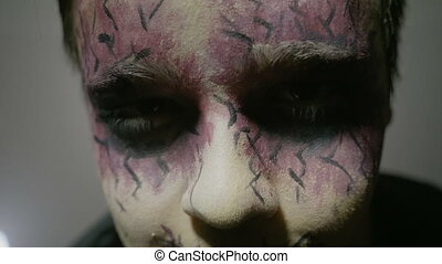 Close up of a young boy wearing halloween zombie face paint...
