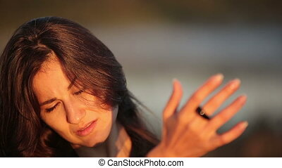 Close Up of a Young Brunette Woman Enjoying the Sun Rays on Her Face During Sunrise