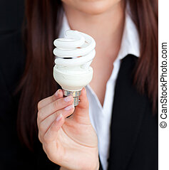 Close-up of a young businesswoman holding a light bulb