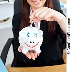 Close-up of a young businesswoman holding a piggibank