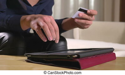 Close-up of a young businesswoman paying bills and using online banking on a tablet pc