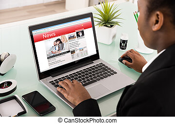 Businesswoman Reading News On Laptop