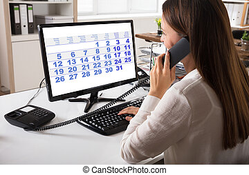 Close-up Of A Young Businesswoman Talking On Landline Phone