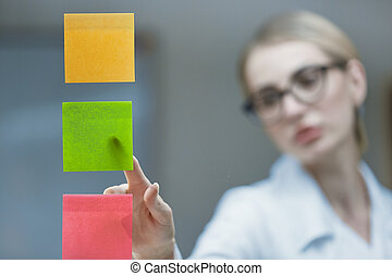 Close-up of a young doctor in an office with a stethoscope around his neck and in a white coat, brainstorming to develop a strategic plan, plastering colorful sticky notes to the transparent glass.