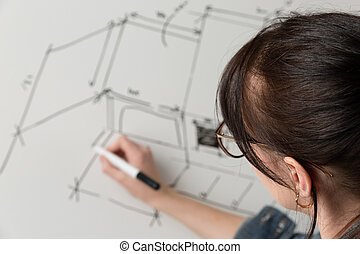 Close-up of a young female architect drawing a sketch for a new famaly home project. Concept of work on technical drawings