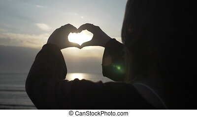 Close up of a young girl back enjoying sunset on the beach and making a heart shape with her hands in slow motion