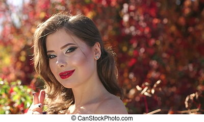 Close-up of a young girl in a beautiful evening dress walking in the autumn park