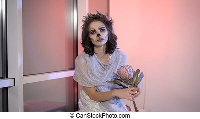 Close up of a young girl with creative scary halloween make. in appearance dead bride sitting on the bench near the window the flower in hands and looking at the camera.
