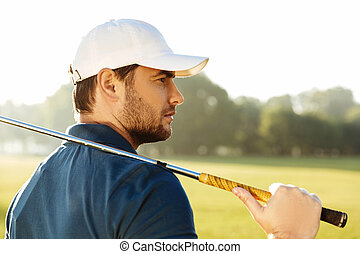 Close up of a young handsome male golfer in hat