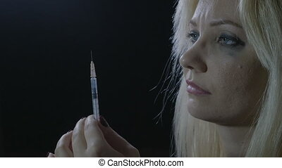 Close up of a young junkie blonde orphan girl preparing her...