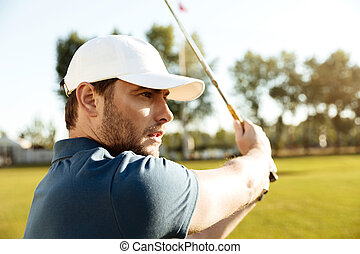 Close up of a young male golfer hitting a fairway shot