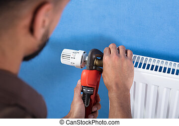 Plumber Using Wrench For Fixing Thermostat