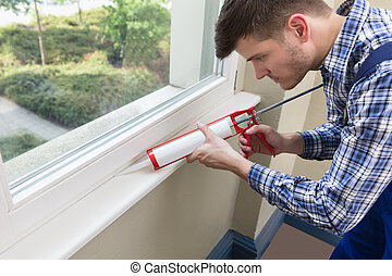 Worker Applying Silicone Sealant With Silicone Gun - Close-...