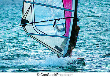 Close up of a young man surfing the wind on a bright summer day