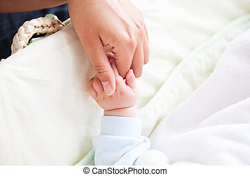 Close-up of a young mother holding her baby's hand at home