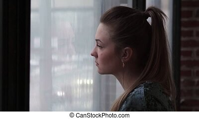 Close-up of a young sad woman looking out the window