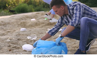 Close-up of a young volunteer gathering garbage on river bank. Volunteer concept