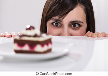 Close-up Of A Young Woman Craving For Slice Of Cake