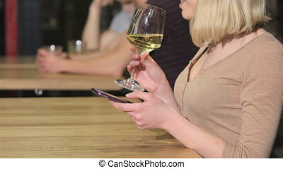 Close up of a young woman drinks wine holding phone in her hand