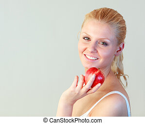 Close-up of a young woman holding an apple with focus on woman