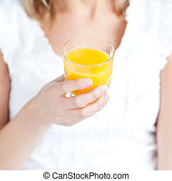 Close-up of a young woman holding an orange juice