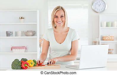 Close up of a young woman looking into camera while cutting peppers in kitchen