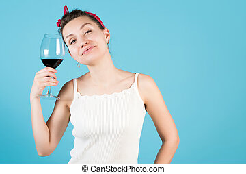 Close-up of a young woman on a blue background, she holds a glass with red wine